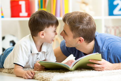 father and his kid son reading a book on floor at home